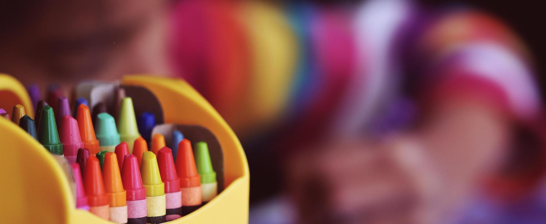 crayons in front of coloring child