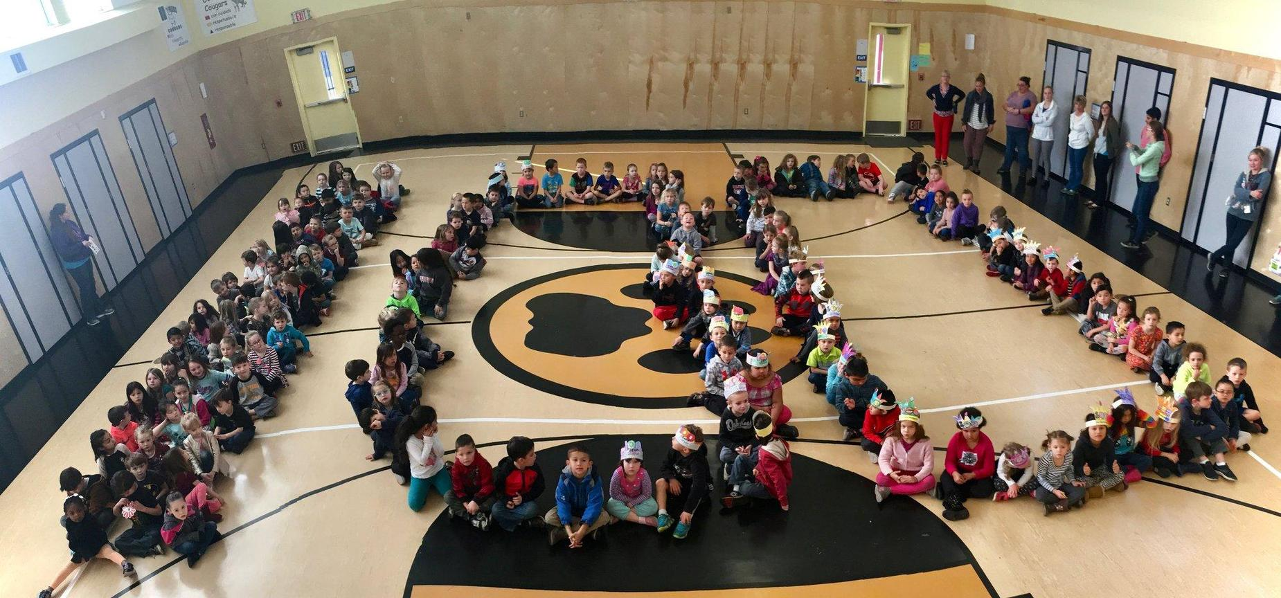 Student at Dow's Prairie form the shape of 100 in multi-purpose room
