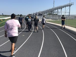 Student walk the track, getting exercise outdoors while socially distanced.