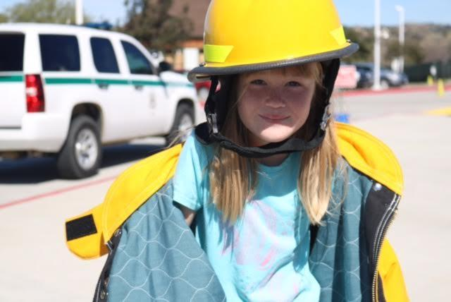 Student in fire gear during Smokey the Bear assembly