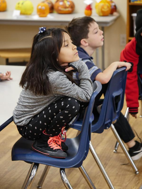 Two students crouching on to of their backward facing classroom chairs as they listen to the teacher.