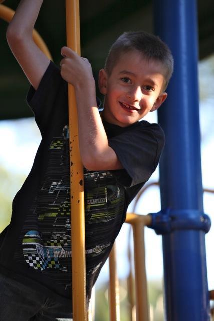 boy hanging on playground equipment