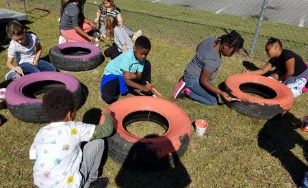 3rd grade students painting tires for garden project