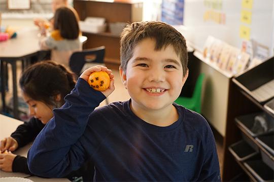 Boy holding orange clove