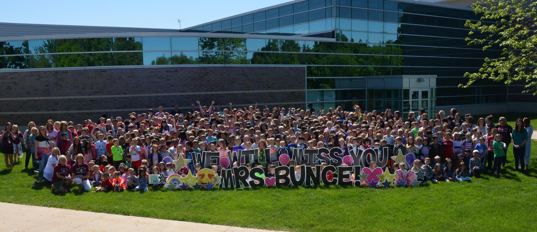 student body stands behind sign that says We Will Miss You Mrs. Bunce on lawn in front of building