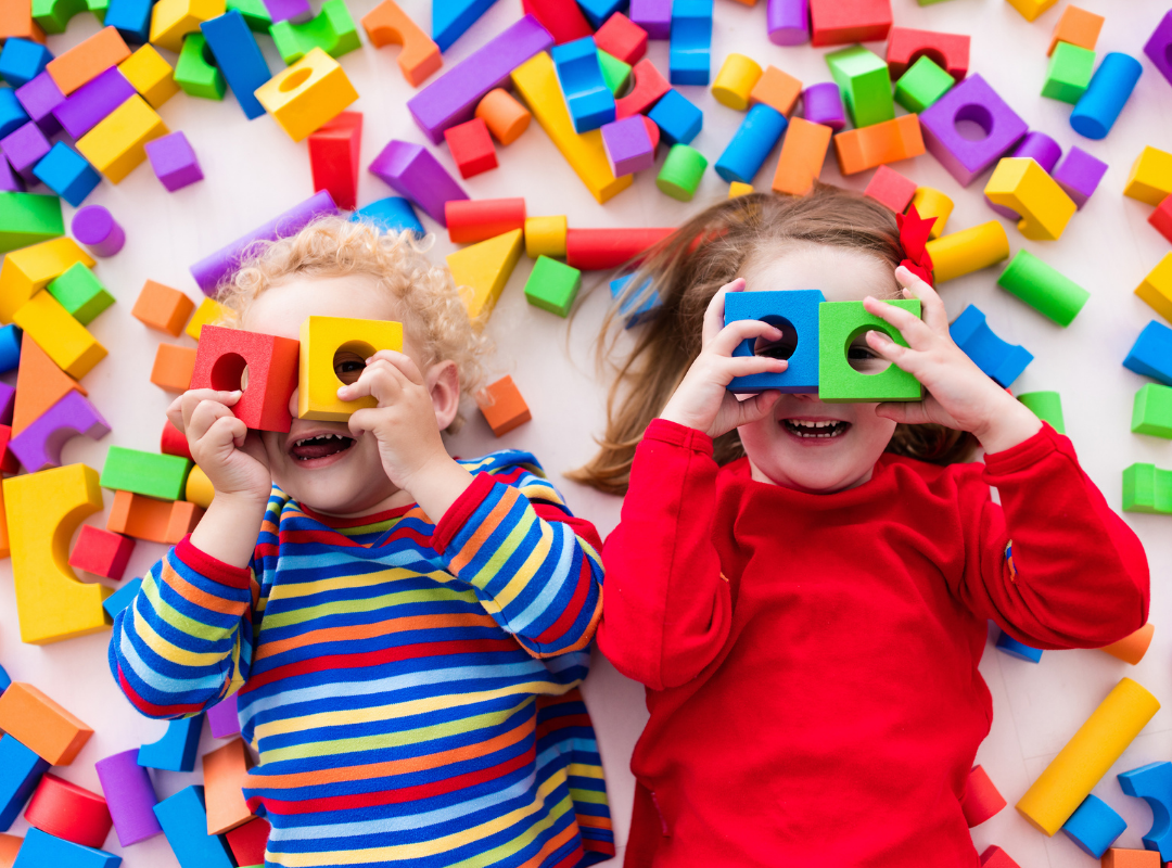 2 kids surrounded by blocks with blocks on their faces covering their eyes