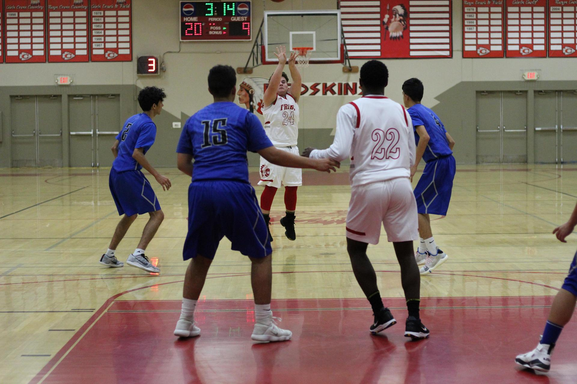 Varsity Boys playing basketball against Caruthers.