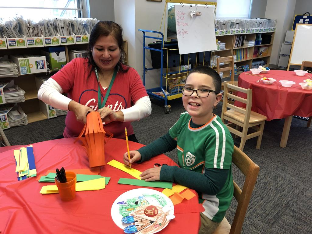 Aide and boy making colored paper lanterns