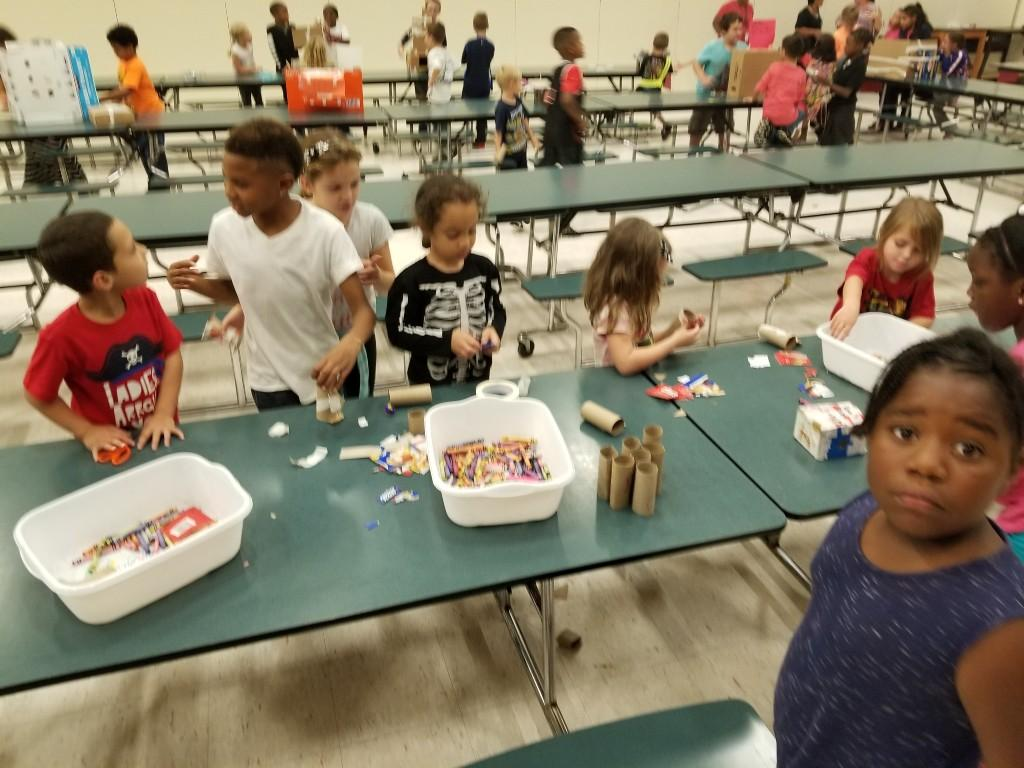 Third grade and kindergarten students working together to create things out of cardboard.