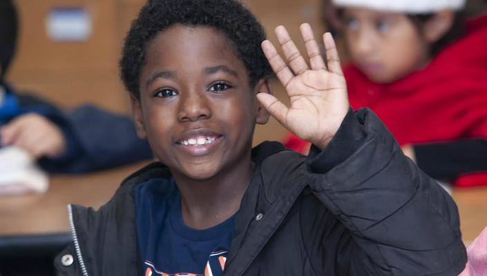 Student waving in class