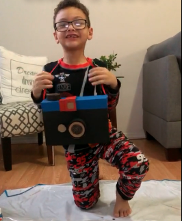 boy with glasses showing his camera box