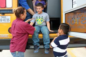 Escobar Rios students learning how to exit a bus through an emergency door.