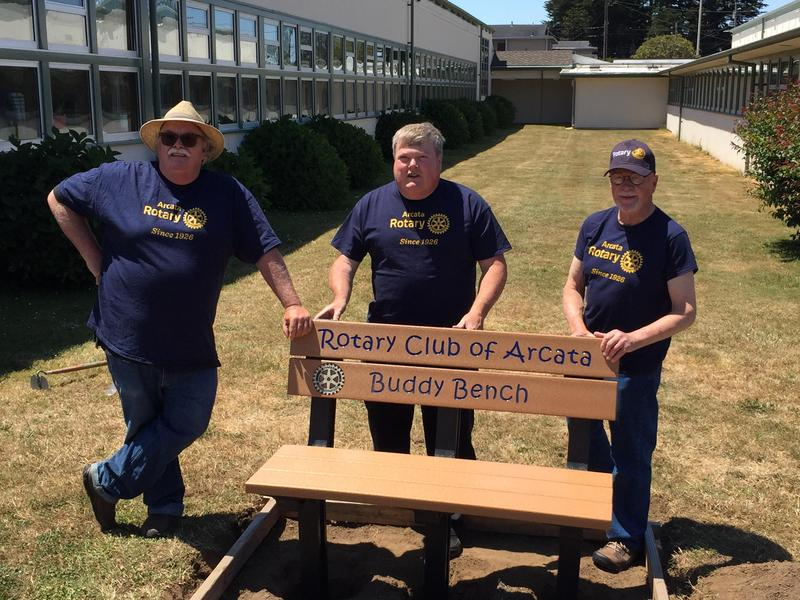 Three member of the Arcata Rotary posing next to the new Buddy Bench at AES