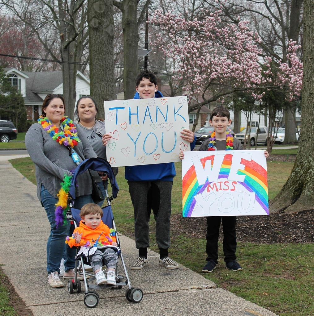 Photo of Washington School family holding signs in support of teachers during car parade.