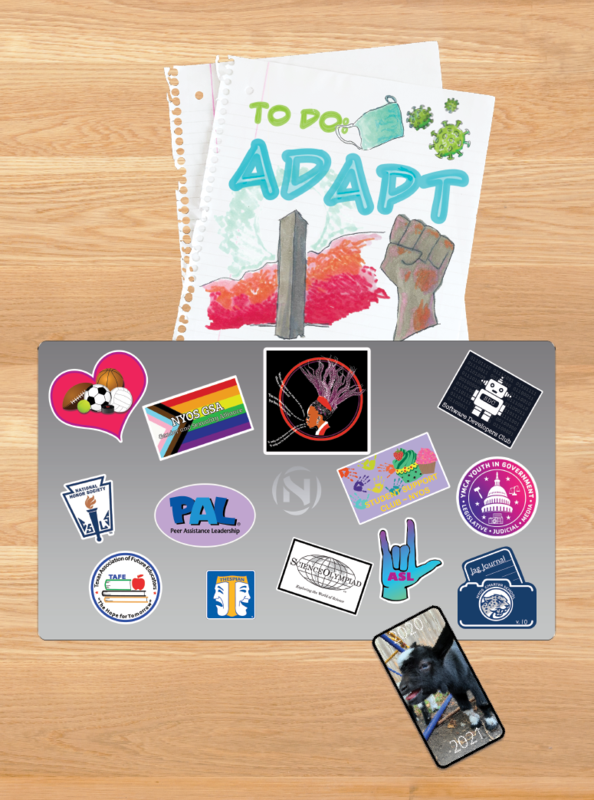 Yearbook cover, which features a NYOS laptop complete with club stickers.