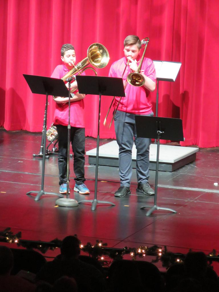 Two male horn players perform at center stage, the auditorium's bright red curtain visible in the back