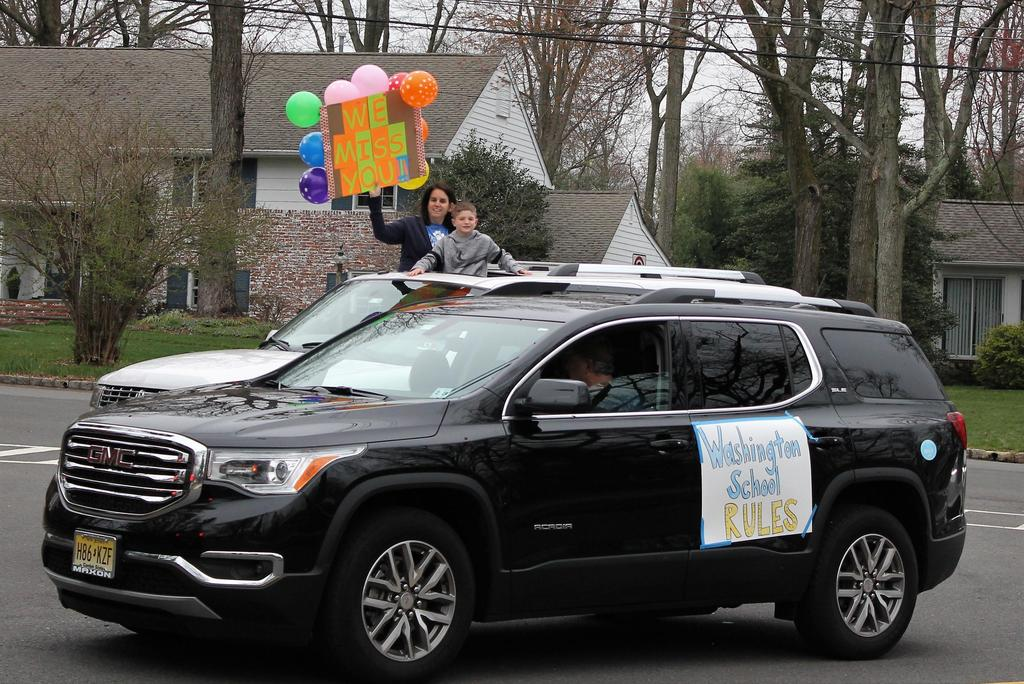 Photo of Washington teacher waving to families during a car parade for students during COVID-19 distance learning.