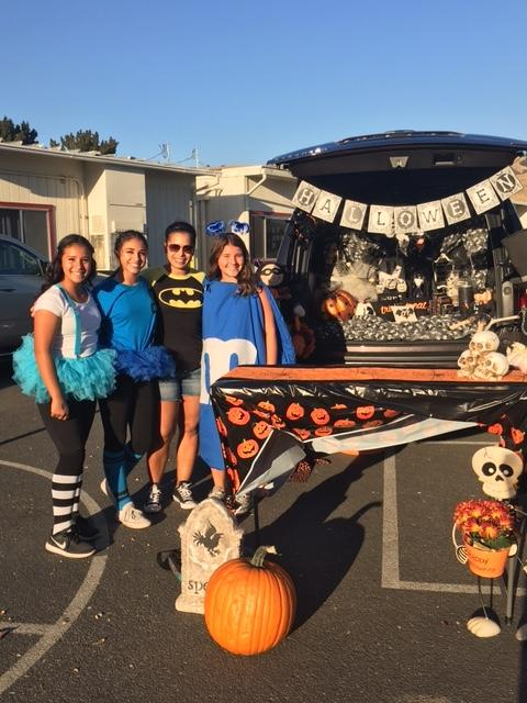 girls standing in front of HAlloween decorated trunk