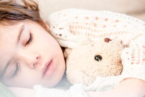 girl-sleeping-with-her-brown-plush-toy-101523.jpg