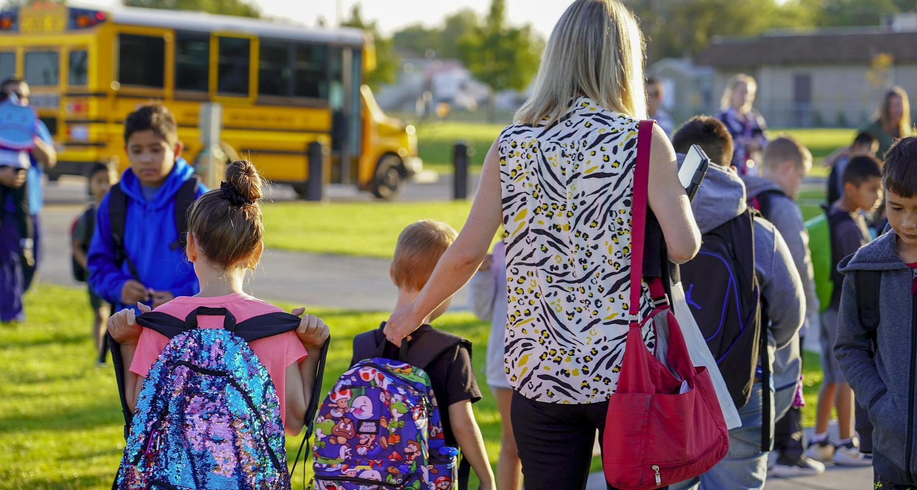 Mom walking child to school.