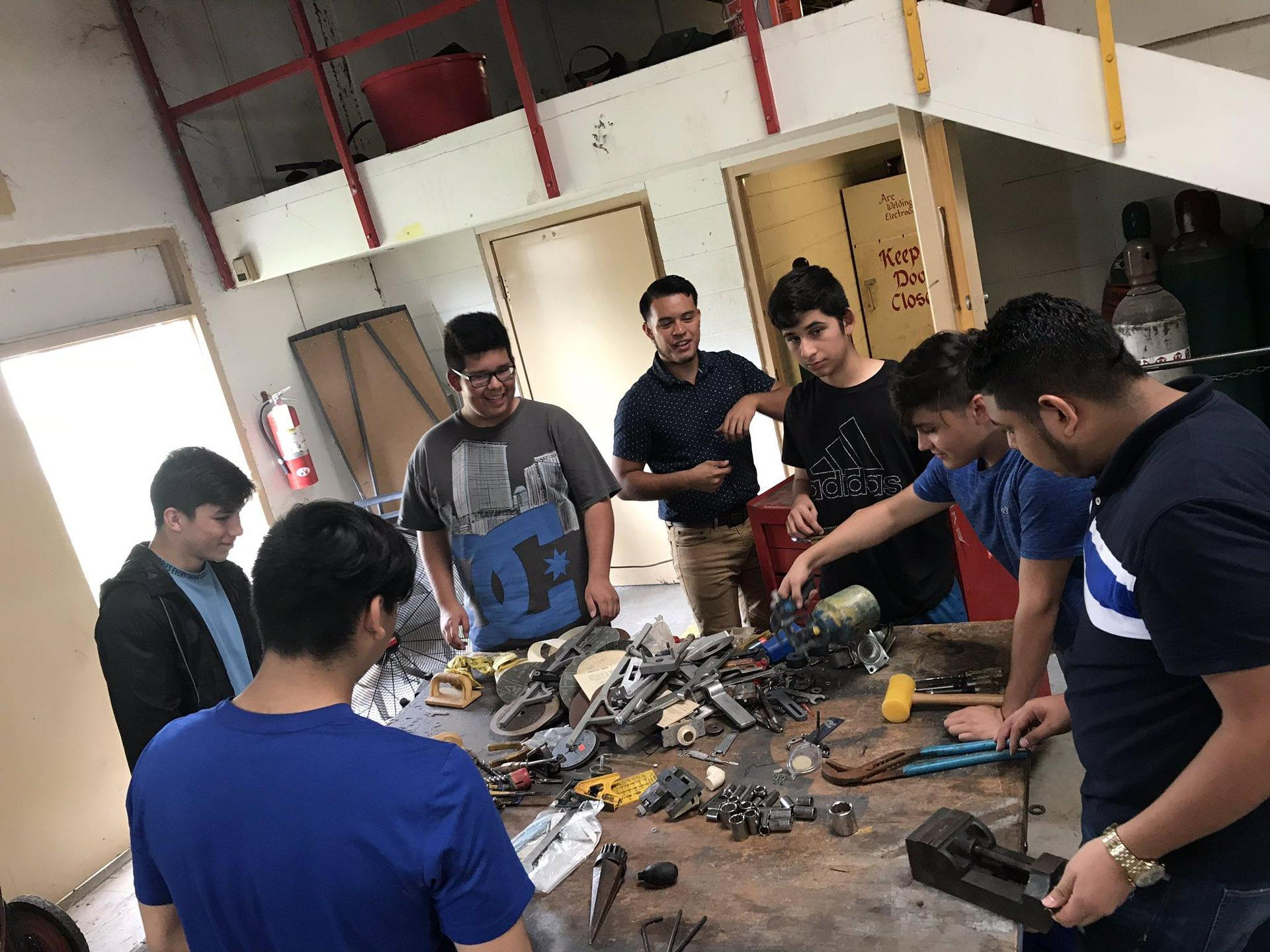 group of students in mechanic shop standing around table with tools