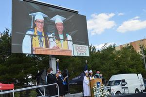 Valedictorian and salutatorian dressed in their white gowns give joint speech to the Class of 2020.