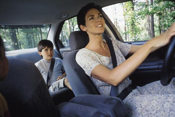 parent in car driving child who is in the back seat