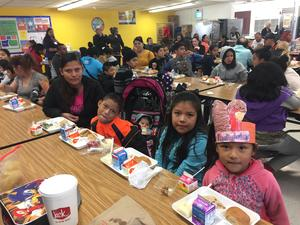 Bonham students enjoying Thanksgiving lunch with mom and baby