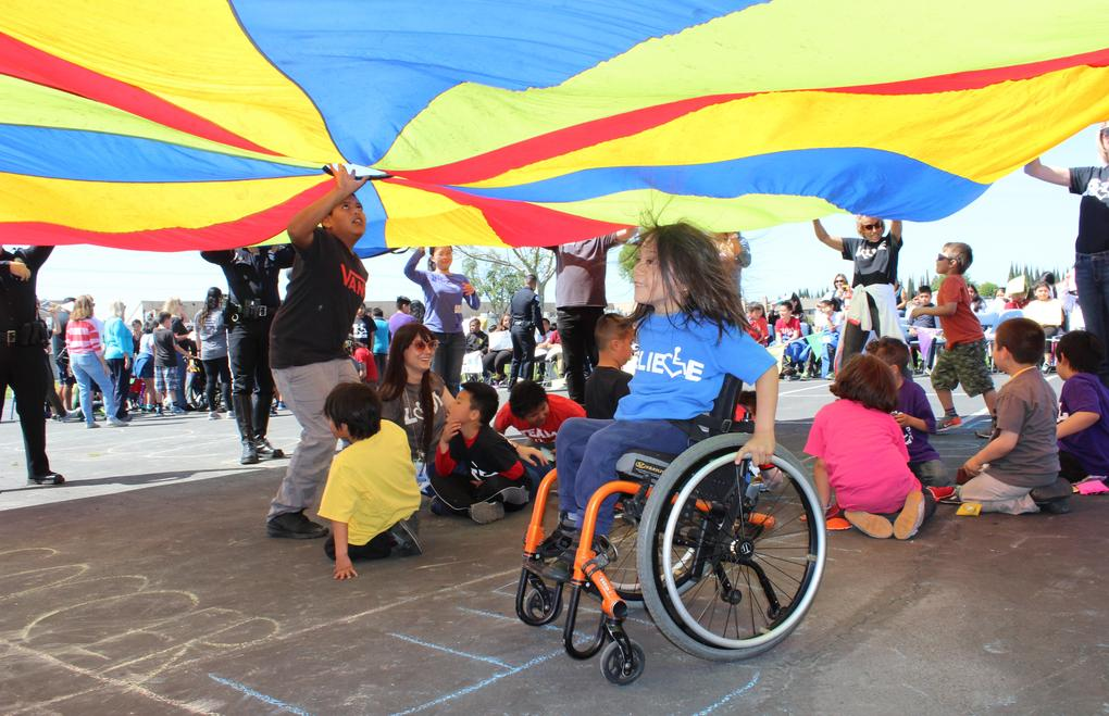 Students and staff play with the big parachute.