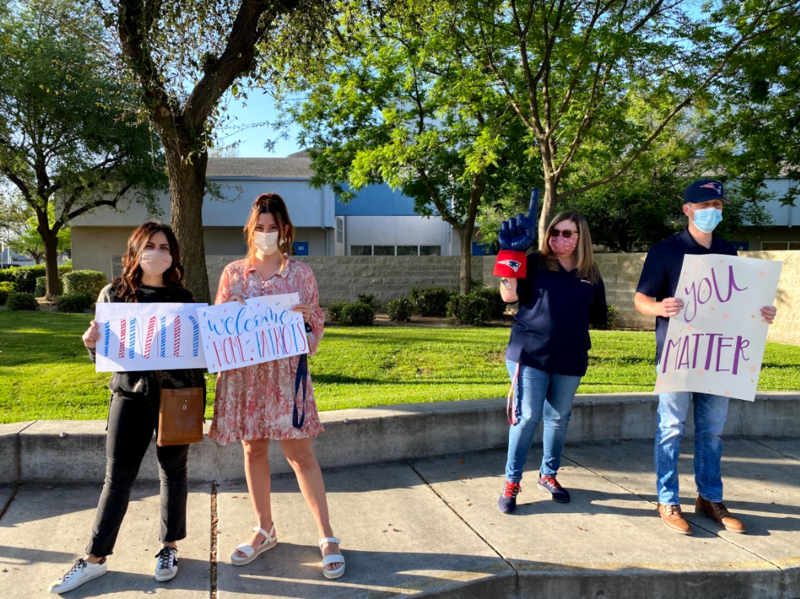 Liberty High School teachers and staff hold encouraging signs welcoming freshman to campus for the first time this year