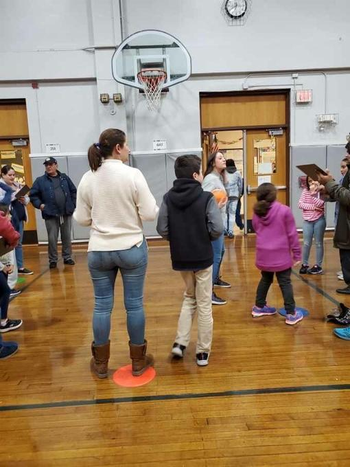 a group of families around the gym basketball math station
