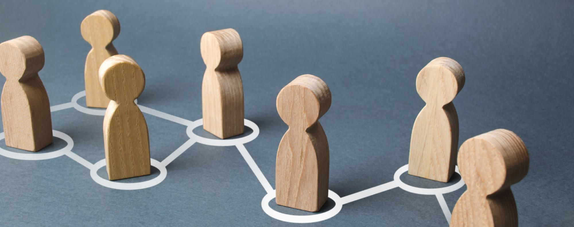 Wood figurines inside chalk circles with interconnecting lines