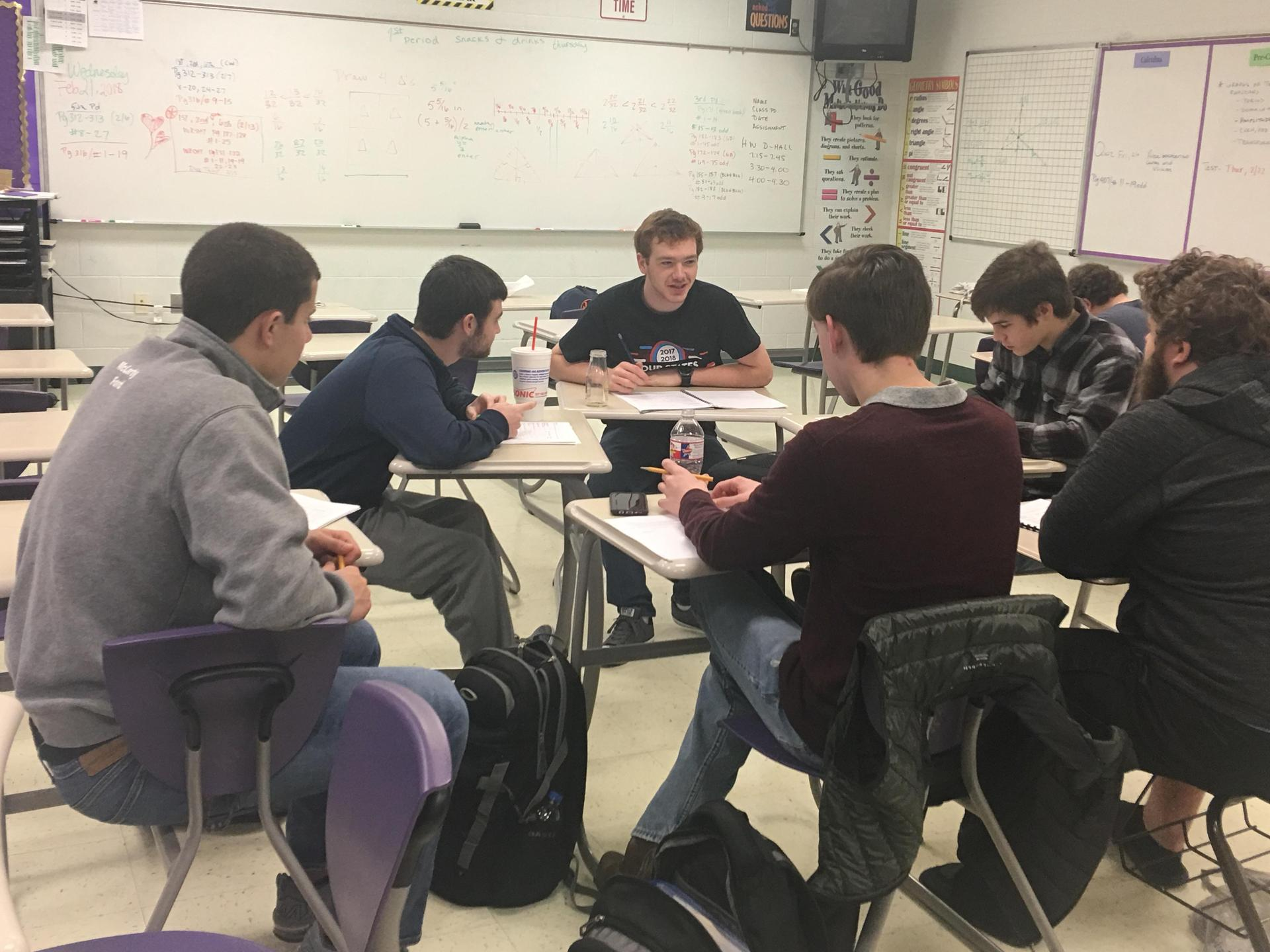 seven students sitting in their desks in a circle having a discussion