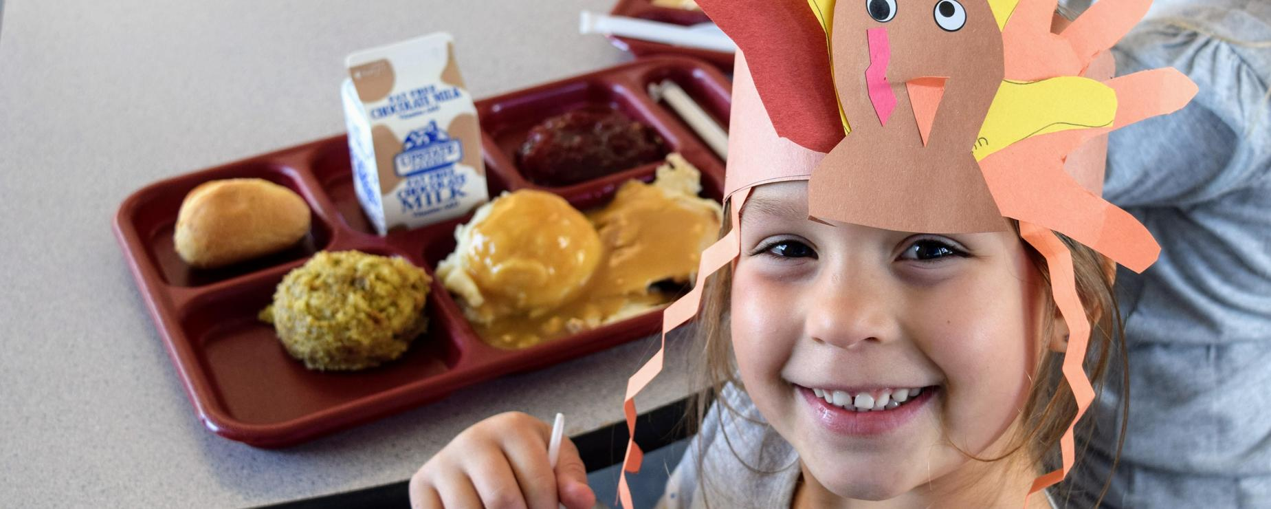 Young student wears a paper turkey hat at Thanksgiving lunch