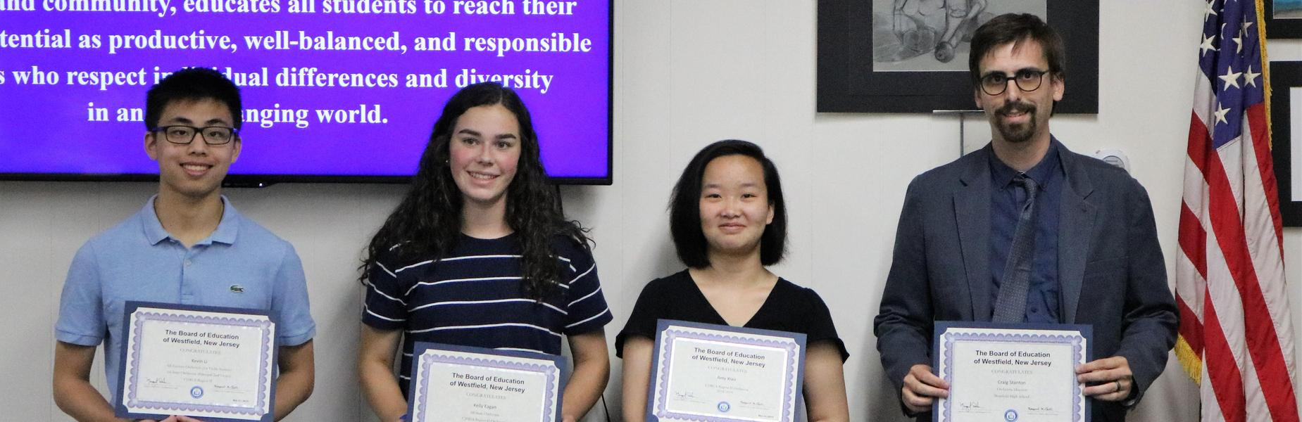 Photo of Westfield High School orchestra students and their instructor holding certificates of recognition at May 21 Board of Education meeting.