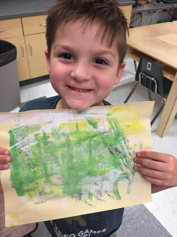 first grade student Bentley shows his watercolor art work