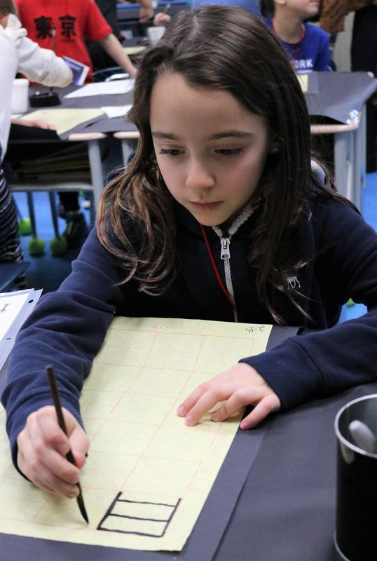 """Photo of Franklin 2nd grader writing Chinese characters on Feb. 21, one of a wide range of activities offered during """"China Day"""" as part of a cultural diversity unit."""