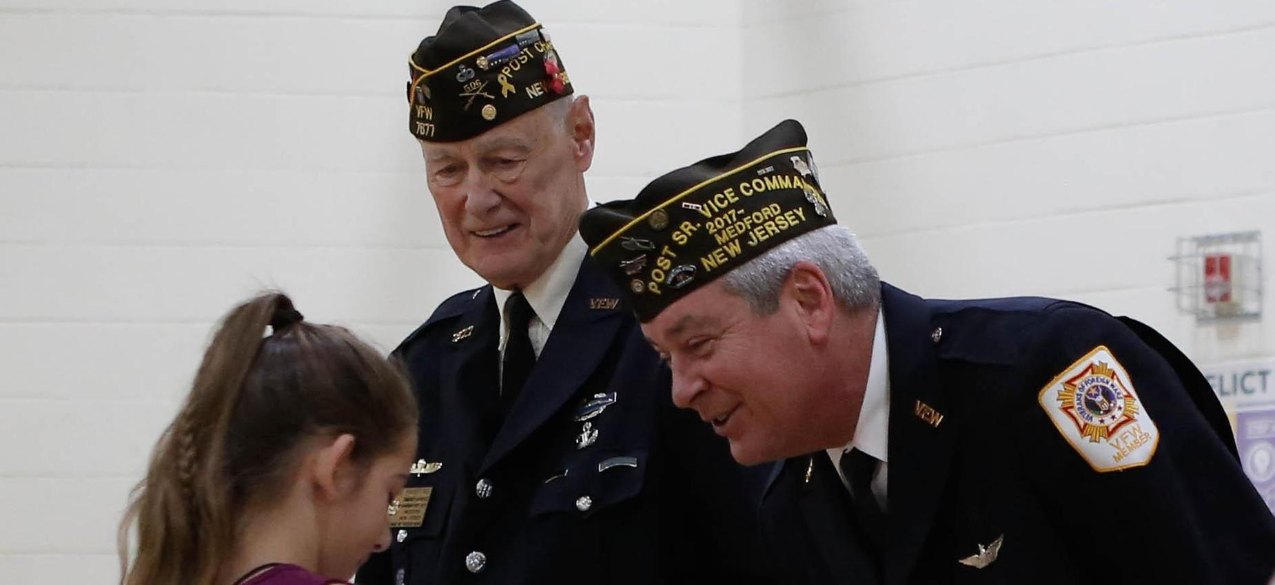 Picture of a student shaking hands with two Veterans during a Veterans Day ceremony 2019
