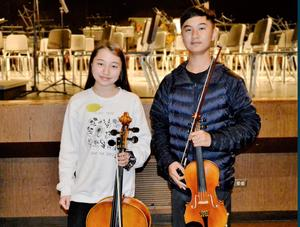 Two Jefferson Middle School orchestra students pose for a picture while holding their violins.