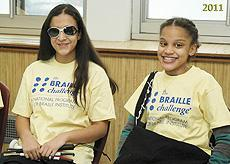 Two female students smiling and wearing Braille Challenge Tee Shirts
