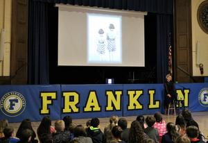 """Franklin 5th graders listen as actor Elizabeth Rainer performs """"Through the Eyes of a Friend"""" on April 1, which is told from the viewpoint of a fictional """"best friend"""" of Anne Frank and uses archival film and sound."""