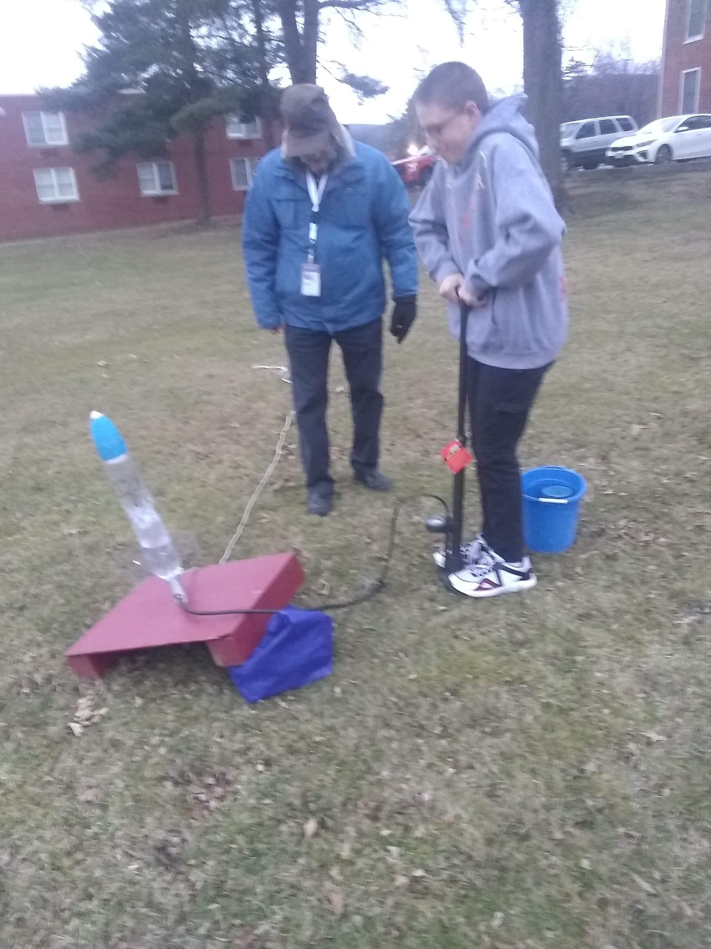 Student pushing down a pump to launch a rocket while an adult looks on