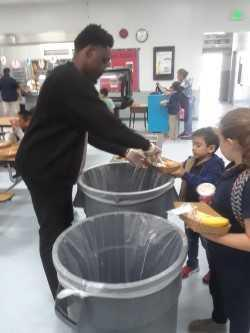 Adult helping a student separate recyclables