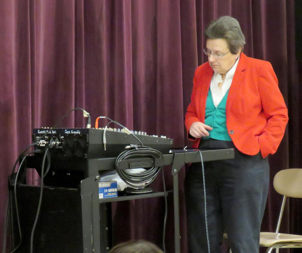 Music teacher and disc jockey Lauren Patrquin-Muise, in a red blazer, plays holiday music