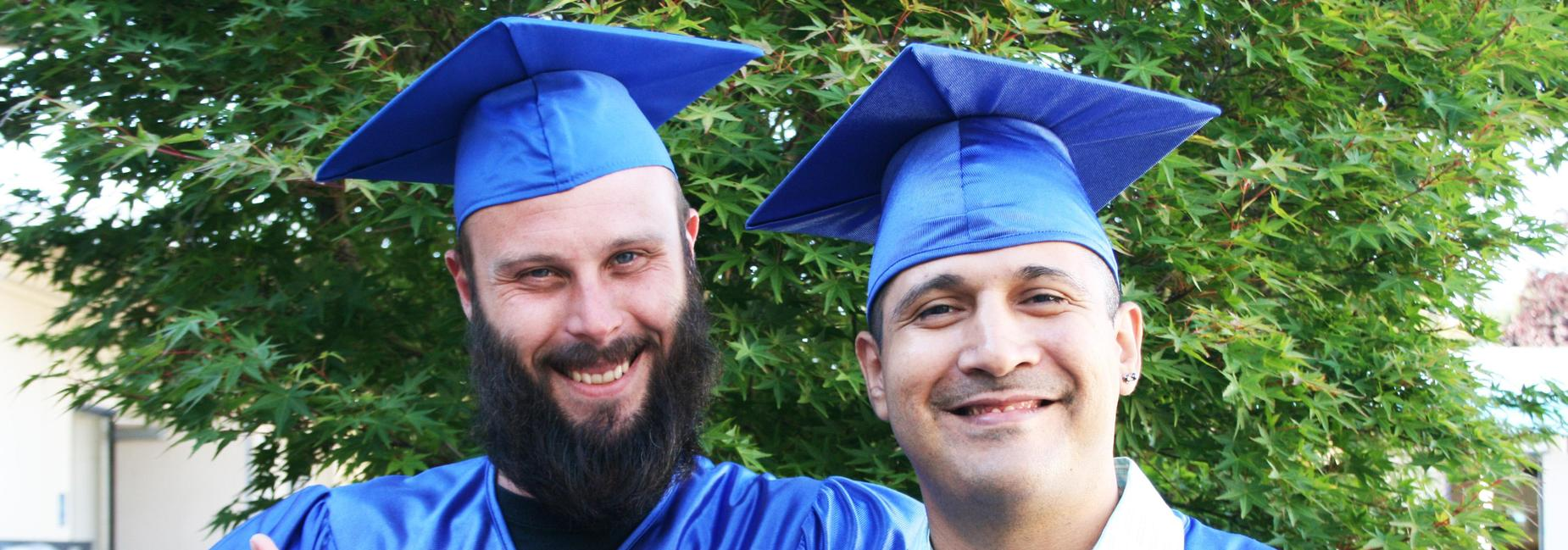 Two diploma graduates in cap and gown smiling at graduation.
