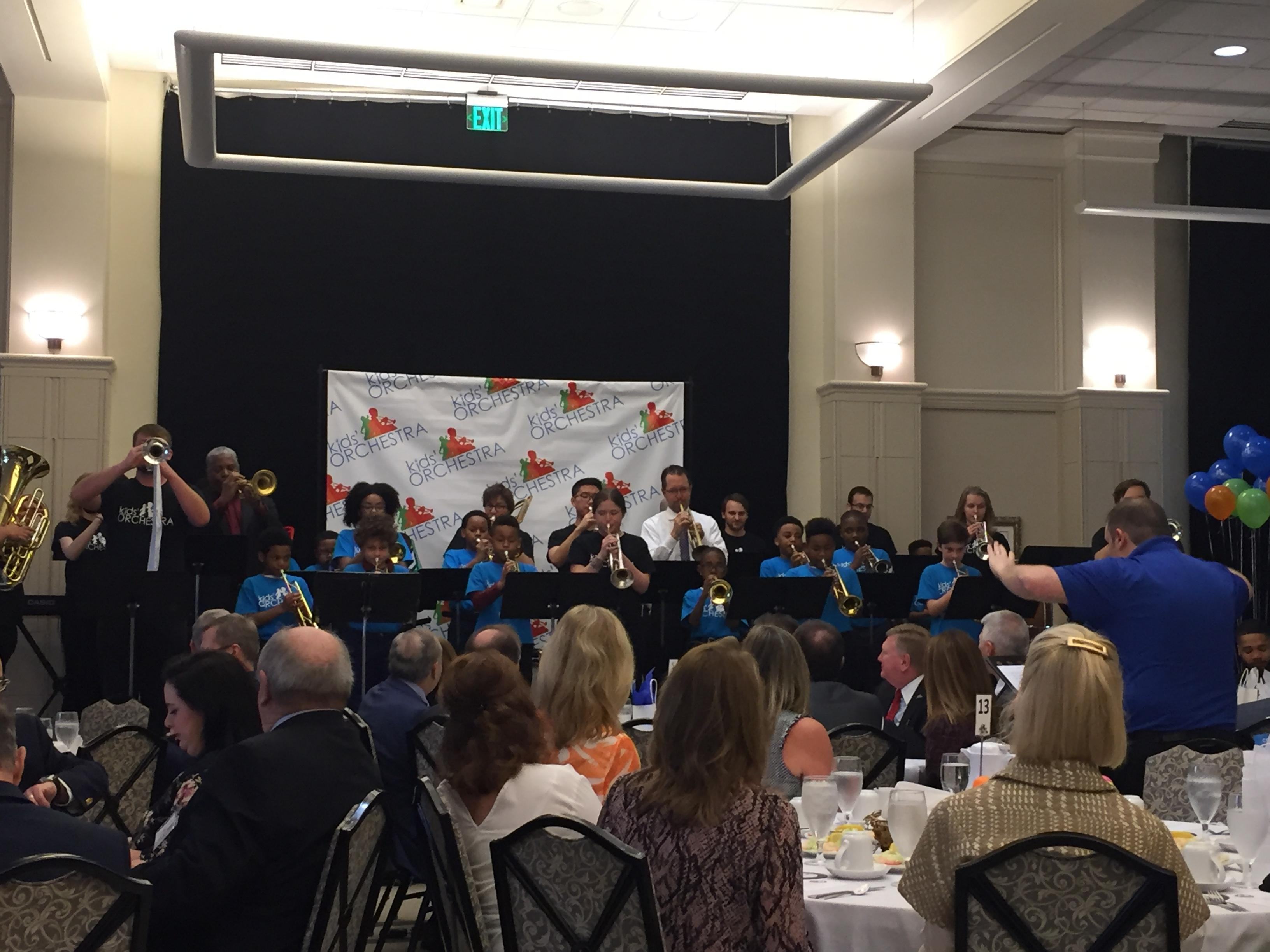 A photo of the a kids orchestral wind ensemble performing at the annual breakfast