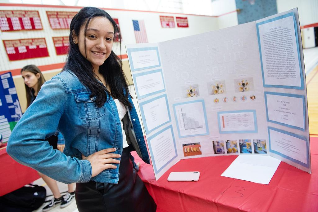 A student stands next to a project about apples and liquids