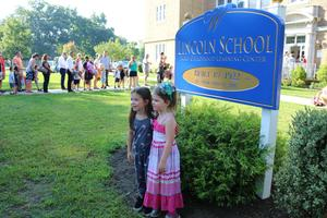 Two kindergarteners pose for pictures in front of the Lincoln School sign on the first day of school.