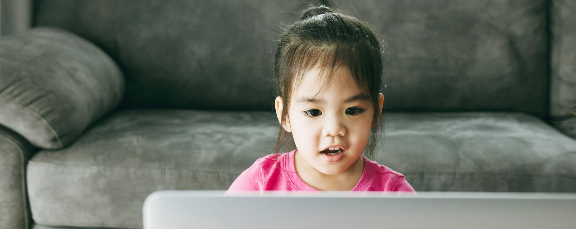 A young girl looking at a laptop