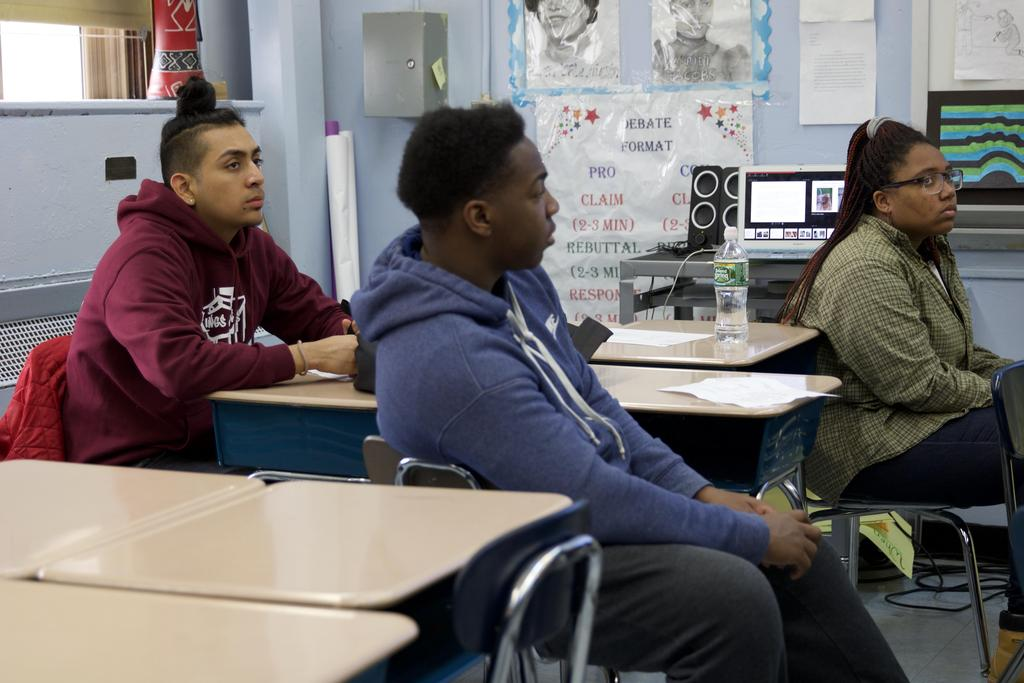three students sitting in their desk